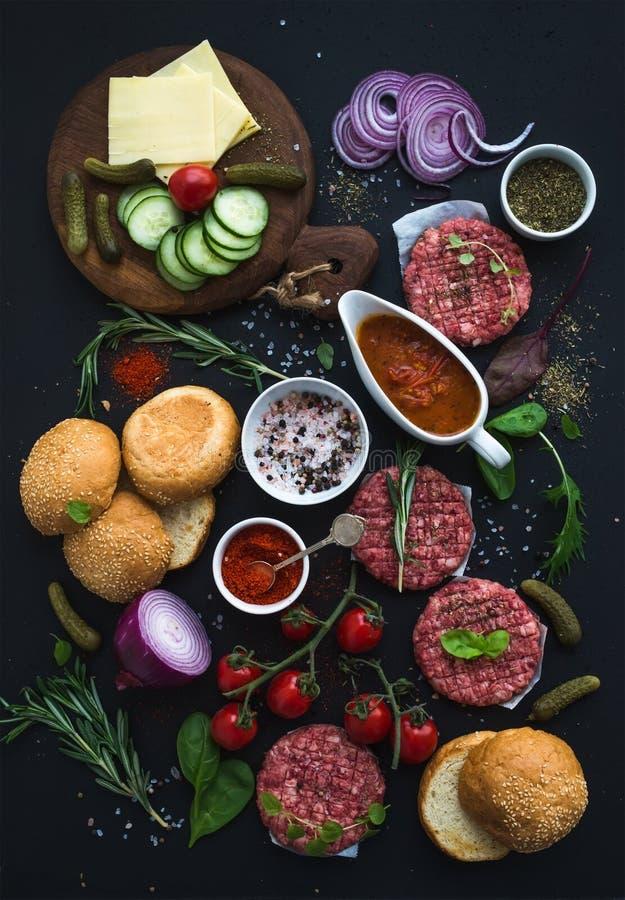 Ingredienser för att laga mat hamburgare Rå jordnötköttköttkotletter, bullar, röd lök, körsbärsröda tomater, gräsplaner, knipor,  royaltyfri foto