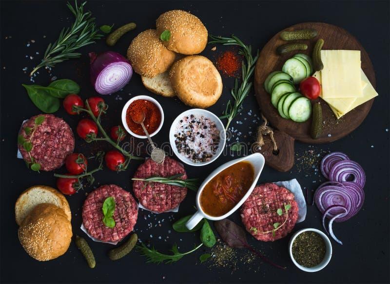 Ingredienser för att laga mat hamburgare Rå jordnötköttköttkotletter, bullar, röd lök, körsbärsröda tomater, gräsplaner, knipor,  royaltyfri bild