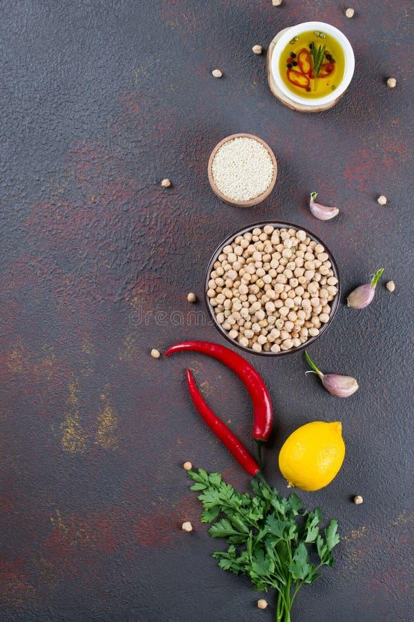 Ingredienser för att laga mat hummus Kikärtar, sesamfrö och olja arkivbild