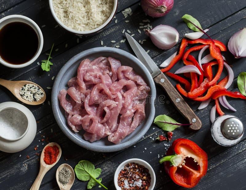 Ingredienser för att laga mat köttuppståndelsesmåfisk med grönsaker och ris - rått kött, söt röd peppar, röd lök, ris, kryddor, p arkivbild