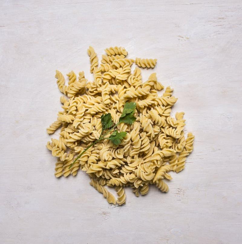 Ingredienser för att laga mat nävepasta på tabellen med bladpersilja på bästa sikt för trälantlig bakgrund royaltyfri fotografi