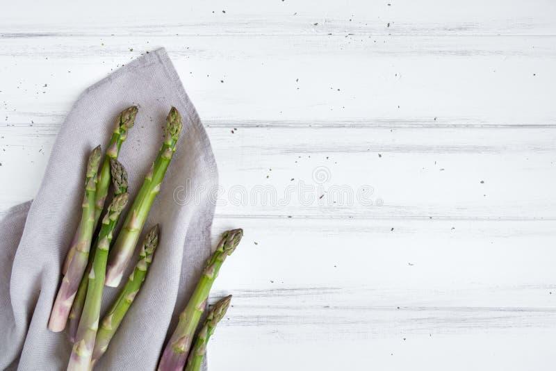 Ingredienser för att laga mat: ny sparris, på linnetorkduken på den vita tabellen Lantlig stilsammansättning Lekmanna- lägenhet,  royaltyfri fotografi