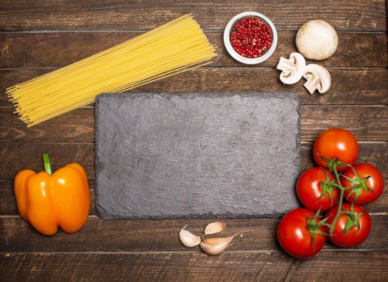 Ingredienser för att laga mat omkring kritiserar brädet Ingredie för pastasås royaltyfri bild