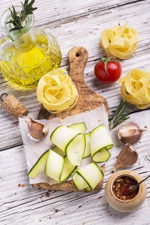 Ingredienser för att laga mat pasta med grönsaker - spagetti, zucchini, tomater, vitlök, rosmarin, peppar royaltyfri bild