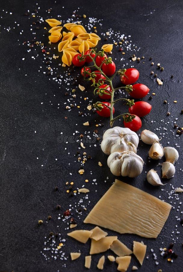 Ingredienser för att laga mat pasta på en svart bakgrund arkivbilder