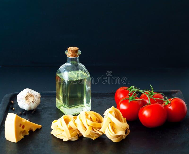 Ingredienser för att laga mat pasta på svart bakgrund Begreppet av italiensk kokkonst royaltyfria foton
