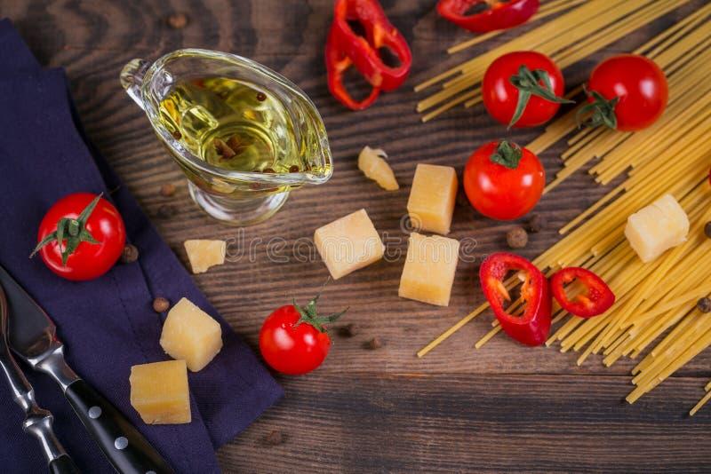 Ingredienser för att laga mat spagetti - rå pasta, tomat, olivolja, kryddor, örter royaltyfri bild