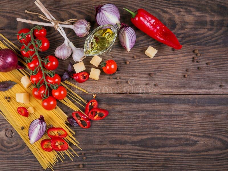 Ingredienser för att laga mat spagetti - rå pasta, tomat, olivolja, kryddor, örter arkivbild