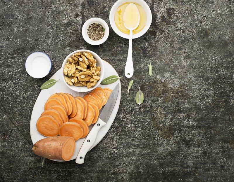 Ingredienser för att laga mat sunda enkla mellanmål från skivor av sötpotatisen, valnötter med honung, innan att baka Top beskåda royaltyfri bild