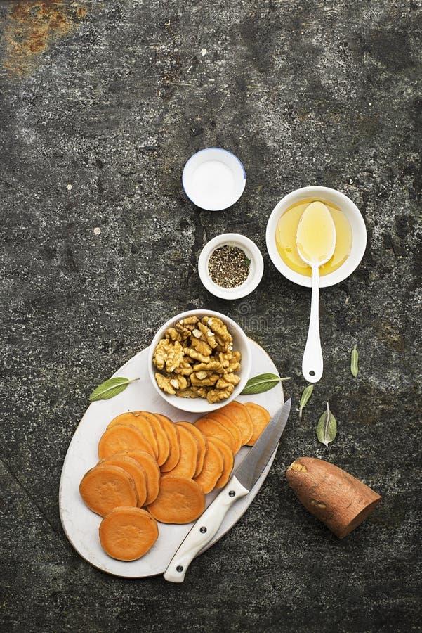 Ingredienser för att laga mat sunda enkla mellanmål från skivor av sötpotatisen, valnötter med honung, innan att baka Top beskåda fotografering för bildbyråer