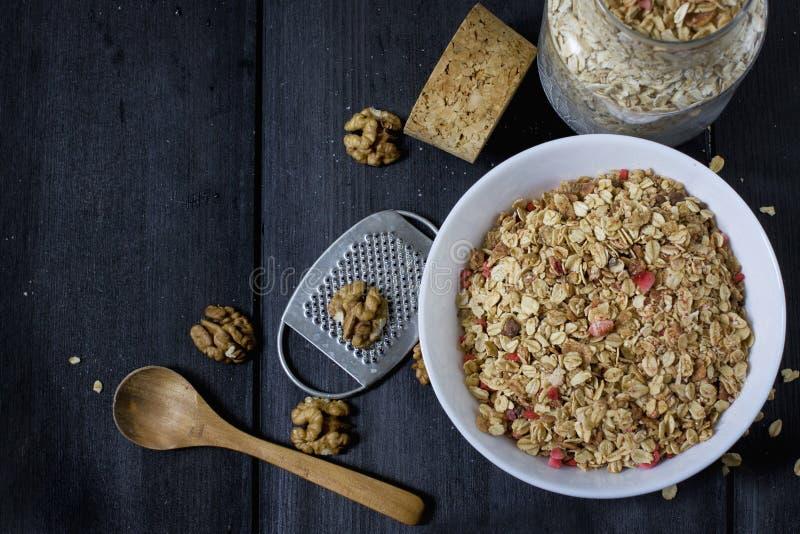 Ingredienser för att laga mat sunda frukostmuttrar, havreflingor, torkade frukter, honung, granola i en vit bunke royaltyfri fotografi