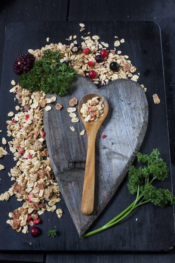 Ingredienser för att laga mat sunda frukostmuttrar, havreflingor, torkade frukter, honung, granola På mörk backgound arkivfoton