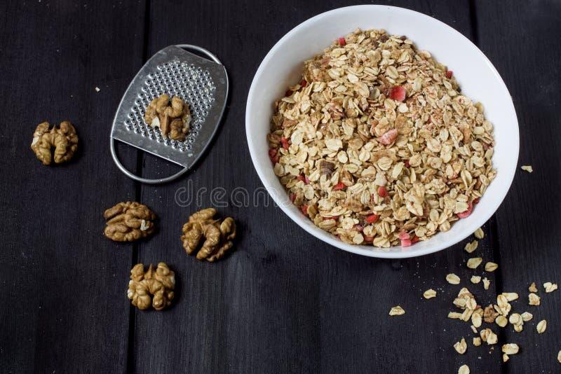 Ingredienser för att laga mat sunda frukostmuttrar, havreflingor, torkade frukter, honung, granola, trähjärta i en vit bunke arkivbilder