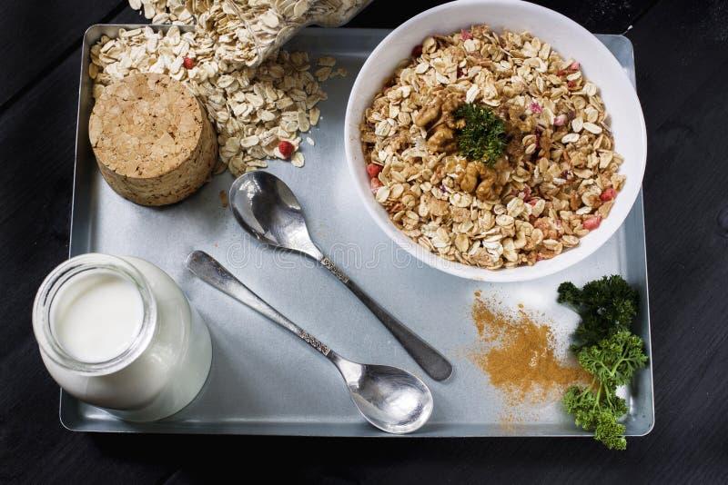 Ingredienser för att laga mat sunda frukostmuttrar, havreflingor, torkade frukter, honung, granola, trähjärta i en vit bunke royaltyfri foto