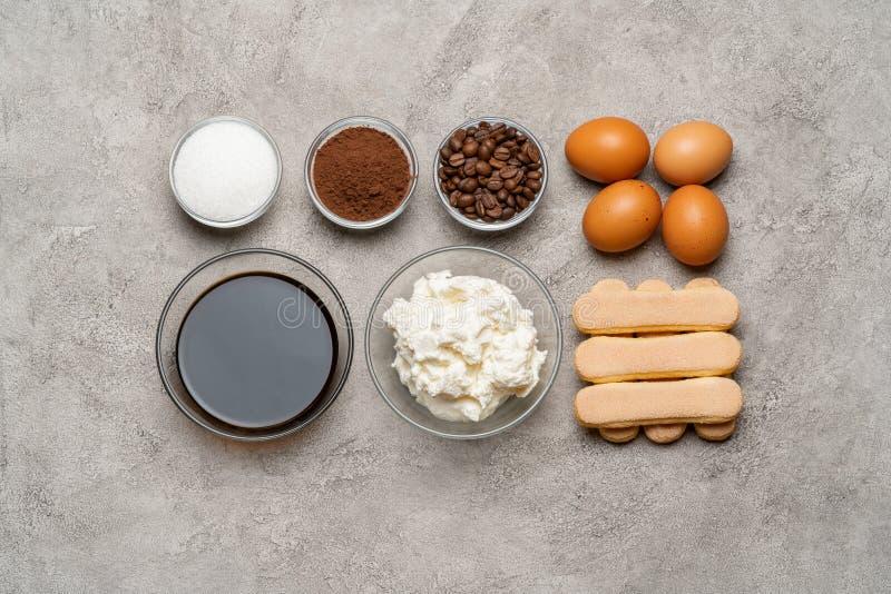 Ingredienser för att laga mat tiramisuen - Savoiardi ljusbruna kakor, mascarpone, ost, socker, kakao, kaffe och ägg arkivbild
