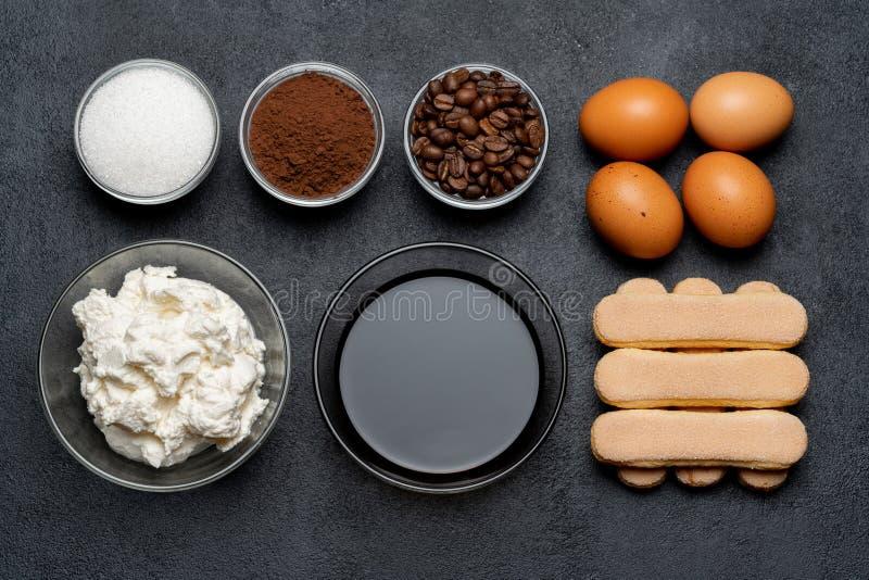 Ingredienser för att laga mat tiramisuen - Savoiardi ljusbruna kakor, mascarpone, ost, socker, kakao, kaffe och ägg arkivfoto