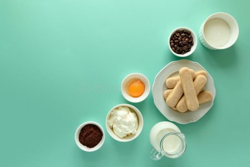 Ingredienser för att laga mat tiramisuen: svampen fingrar kakor Savoiardi, sockerkaksbit i form av ett finger, kexet, mascarponen arkivbilder