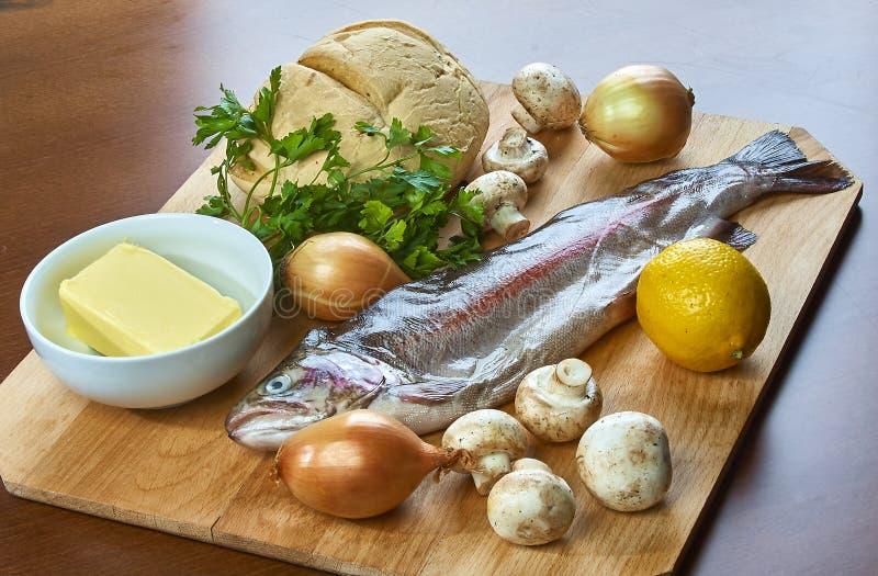 Ingredienser för att laga mat välfyllt bröd för smör för sallad för fiskchampinjonlök arkivbild