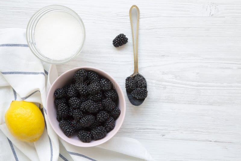 Ingredienser för björnbärdriftstopp: bär citron, socker på en vit träbakgrund Från över över huvudet royaltyfri fotografi