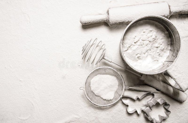Ingredienser för deg - sålla mjöl, kavlen, kakaskärare arkivfoton