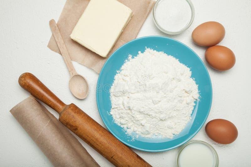 Ingredienser för degen, ägg, mjölkar, smör, saltar och pudrar på den vita tabellen royaltyfria foton