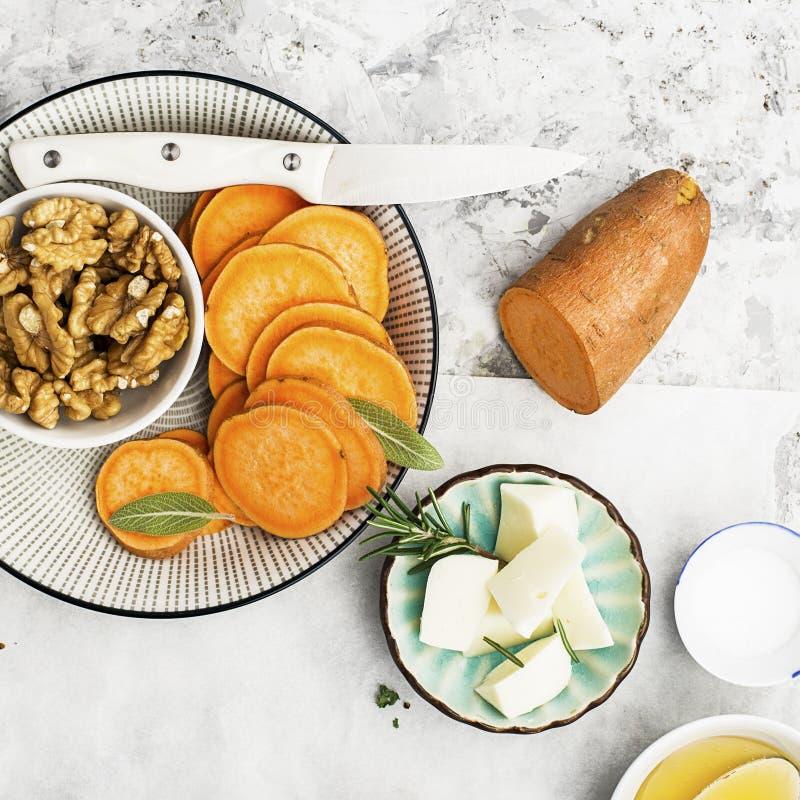 Ingredienser för ett sunt och bekvämt bantar: skivor av den nya rå sötpotatisen, honung, valnötter, rosmarinost, vis man royaltyfria foton