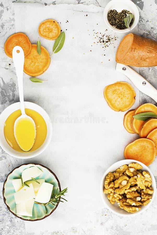 Ingredienser för ett sunt och bekvämt bantar: skivor av den nya rå sötpotatisen, honung, valnötter, rosmarinost, vis man royaltyfri fotografi