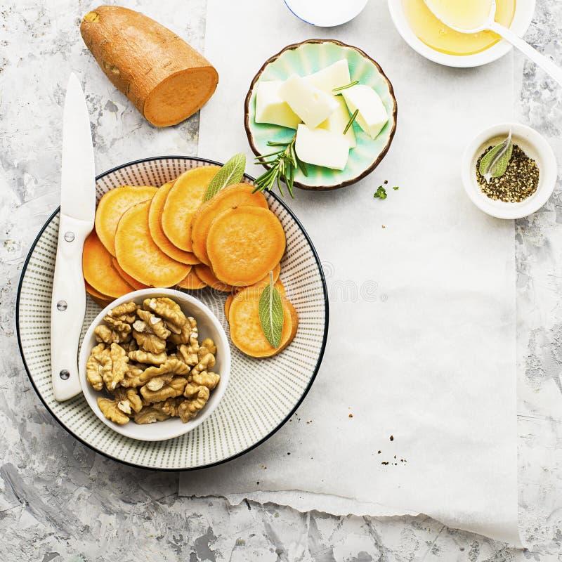 Ingredienser för ett sunt och bekvämt bantar: skivor av den nya rå sötpotatisen, honung, valnötter, rosmarinost, vis man fotografering för bildbyråer