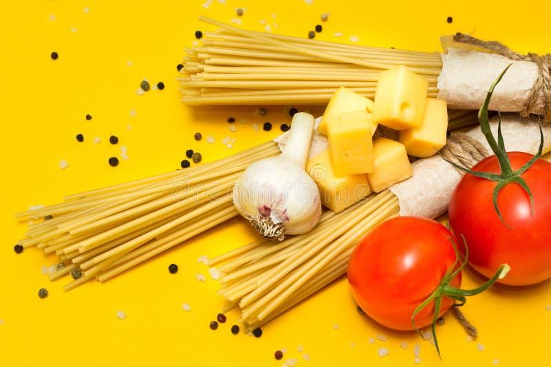 Ingredienser för förberedelsen av pasta Spagetti ost, tomater, vitlök, på en gul bakgrund arkivbild