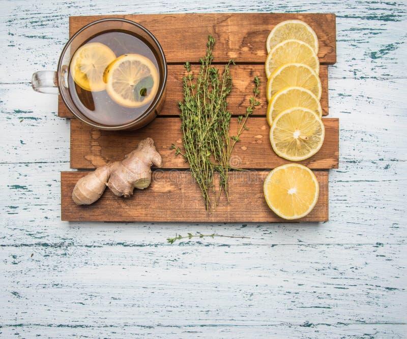 Ingredienser för framställning av doftande te på ett trämagasin, ingefära, citron, mintkaramell och kanel på en vit lantlig bakgr royaltyfria bilder