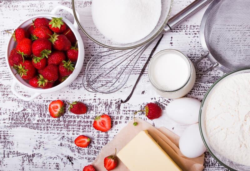 Ingredienser för framställning av jordgubbeyoghurtkakan på vita trälodisar royaltyfri foto