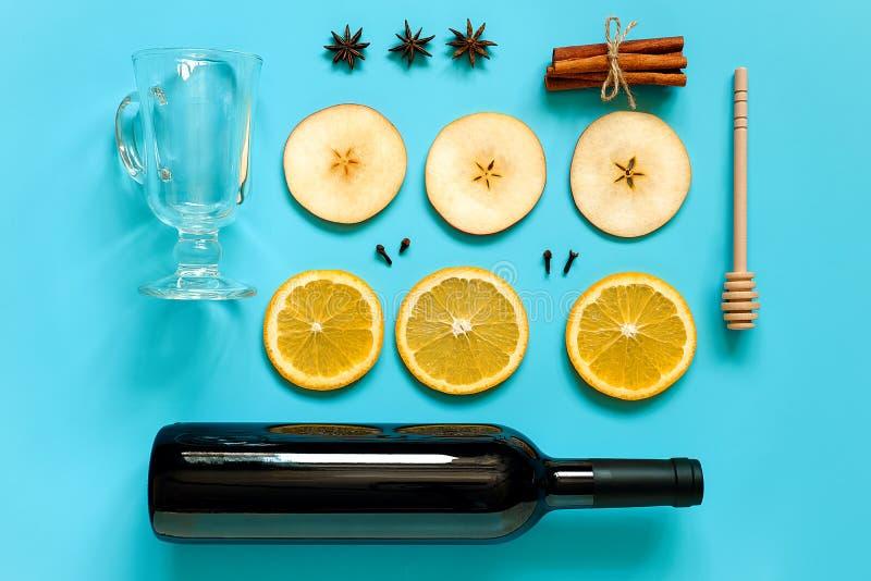 Ingredienser för funderat vin, stilleben på blå bakgrund Flaskan av vin, kanelbruna pinnar, skivor av apelsinen, äpplet, anis och royaltyfri fotografi