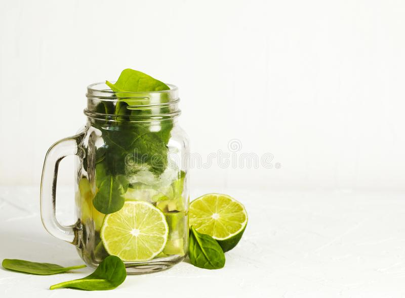 Ingredienser för grön spenatavokadoSmoothie i murarekrus arkivbild