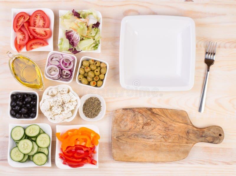 Ingredienser för grekisk sallad i bunkar royaltyfri foto