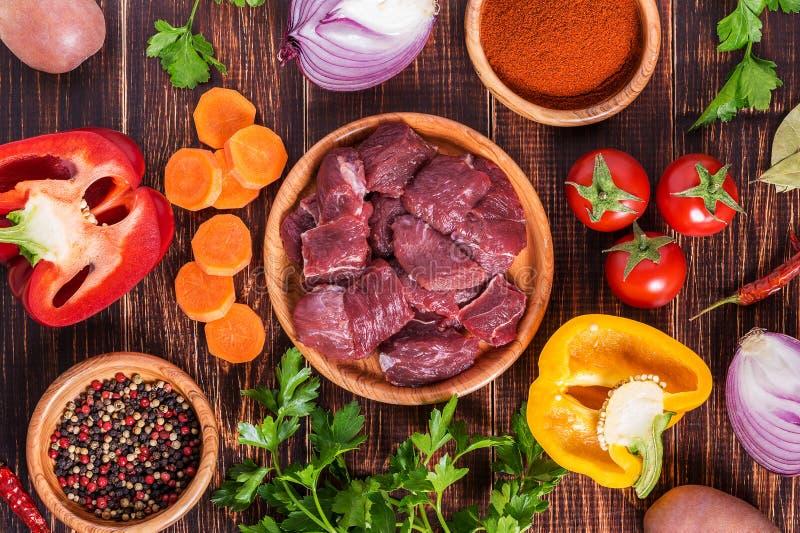 Ingredienser för gulaschmatlagning: rått kött, örter, kryddor, grönsaker arkivbilder