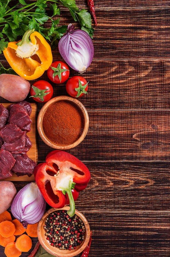 Ingredienser för gulaschmatlagning: rått kött, örter, kryddor, grönsaker royaltyfria bilder