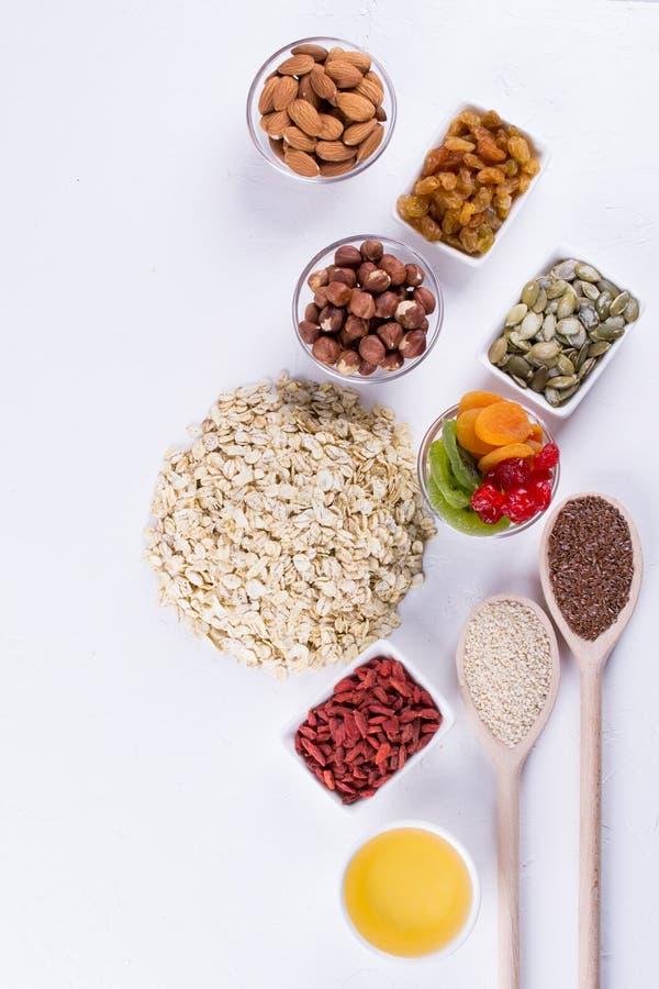 Ingredienser för hemlagad havremjölgranola Havreflingor, honung, muttrar som torkas - frukt och frö arkivbild