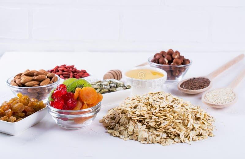 Ingredienser för hemlagad havremjölgranola Havreflingor, honung, muttrar som torkas - frukt och frö sund frukost arkivfoton