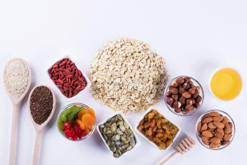 Ingredienser för hemlagad havremjölgranola Havreflingor, honung, muttrar som torkas - frukt och frö sund frukost arkivfoto