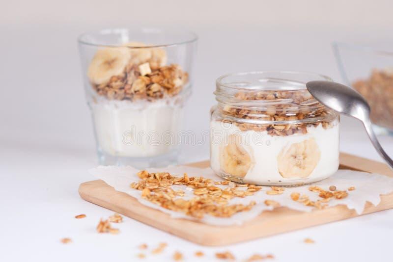 Ingredienser för hemlagad havremjölgranola i den glass kruset Havreflingor, honung, russin och muttrar sunt frukostbegrepp fotografering för bildbyråer