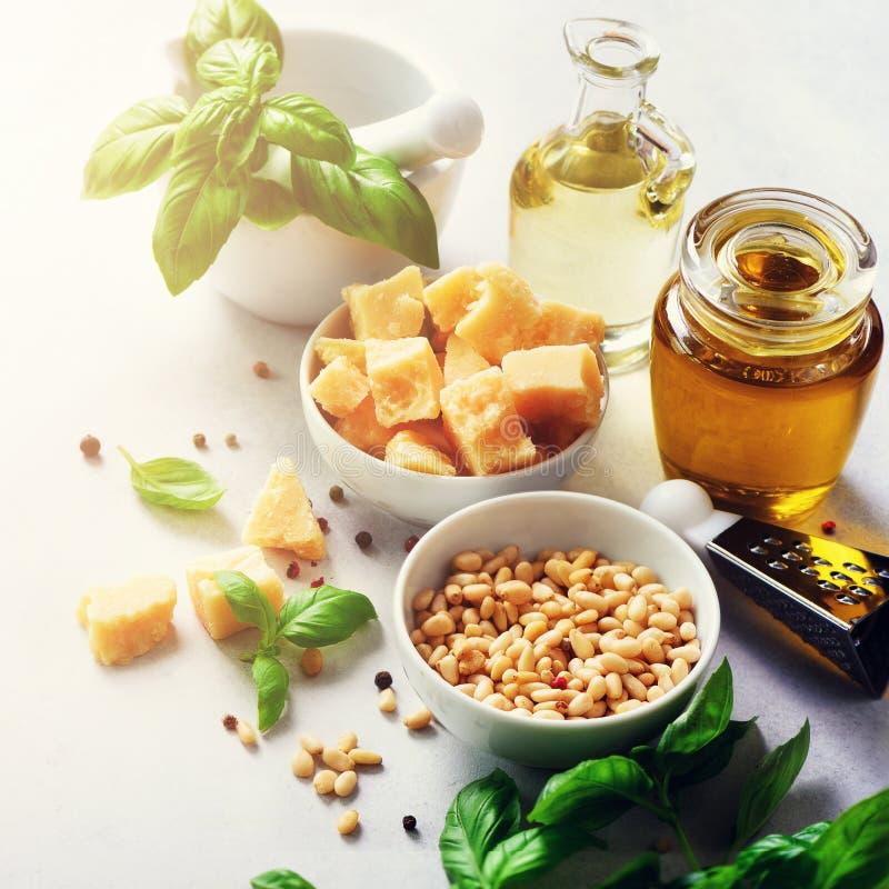 Ingredienser för hemlagad pesto - basilika, citronen, parmesan, sörjer muttrar, vitlök, olivolja och saltar på vitbetong royaltyfri bild