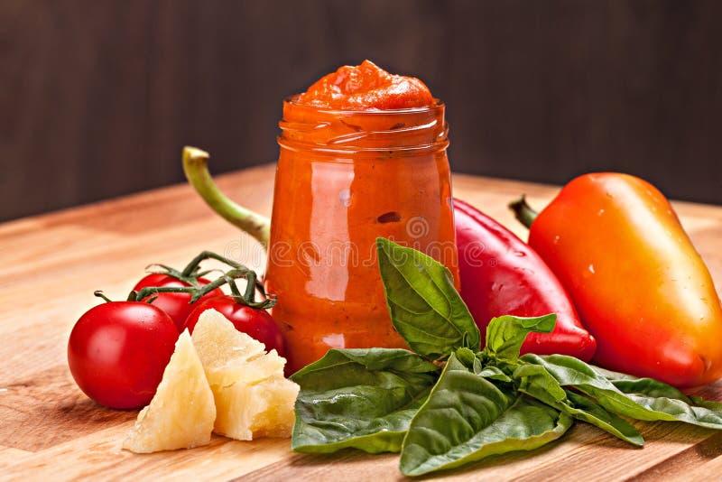 Ingredienser för italiensk röd såspesto och en krus av pesto arkivfoton