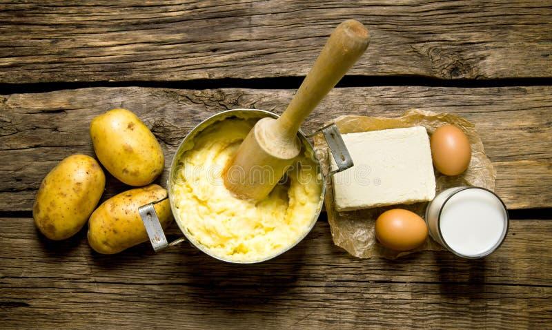 Ingredienser för mosade potatisar - ägg, mjölkar, smör och potatisar på träbakgrund arkivbilder