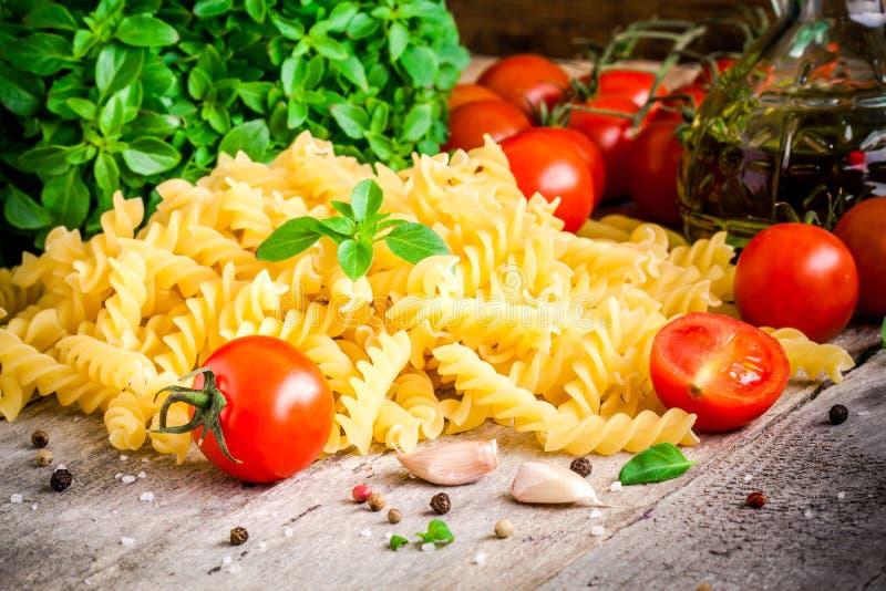 Ingredienser för pasta: organiska körsbärsröda tomater, ny basilikafusilli, vitlök och olivolja royaltyfri bild