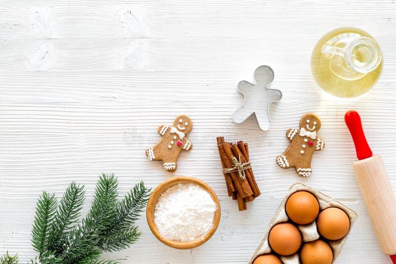 Ingredienser för pepparkakakakor för nytt år Ägg, mjöl, kanel, olja nära pepparkakaman, kavel och gran arkivbild