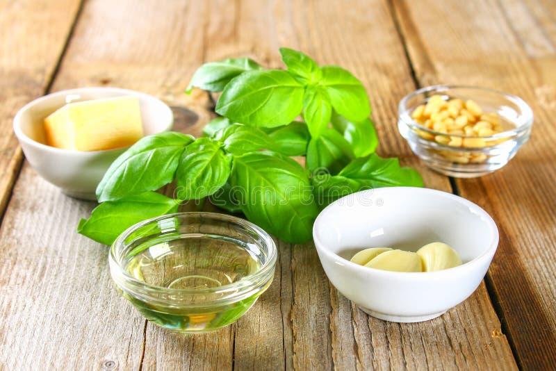 Ingredienser för pestosås Ost vitlök, basilika, sörjer muttrar, olivolja arkivbild