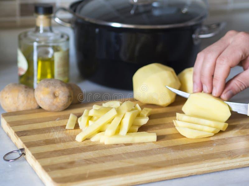 Ingredienser för pommes frites person som hugger av potatisar på brädet med kniven royaltyfri bild