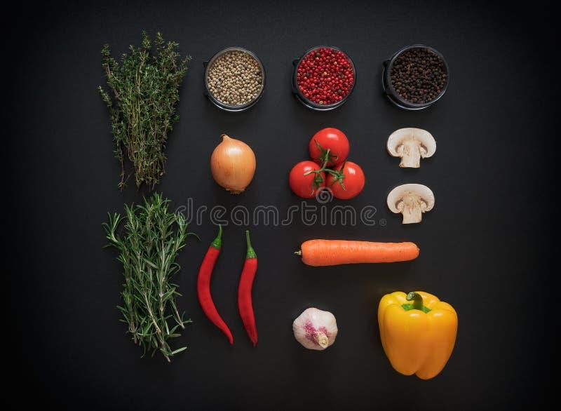 Ingredienser för smaklig salladdanande: grönsallatsidor, champignons, tomater, örter och kryddor på mörk lantlig bakgrund arkivfoto