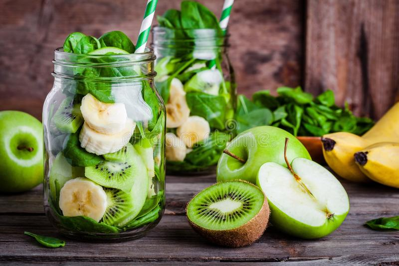 Ingredienser för smoothie i krus: banan kiwi, spenat, grönt äpple royaltyfria bilder