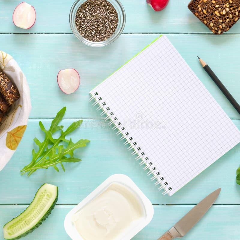 Ingredienser för strikt vegetariansmörgås med gräddost, nytt gurka-, rädisa- och chiafrö på mintkaramellträbakgrund royaltyfria bilder